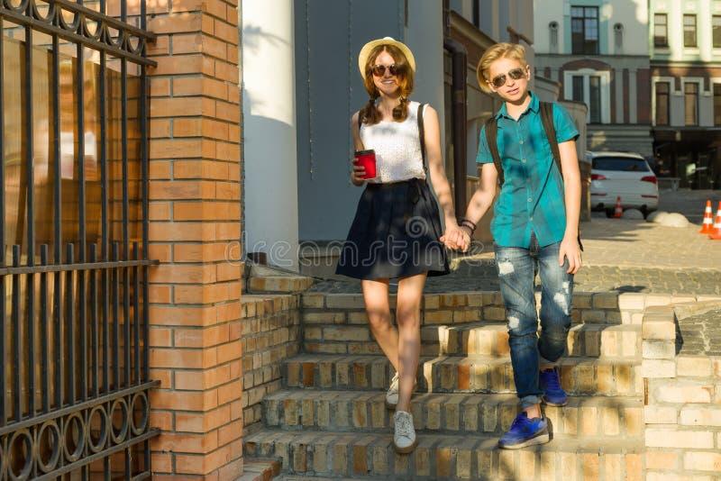 Par av tonåringar går till och med gatorna av staden som rymmer händer royaltyfri fotografi