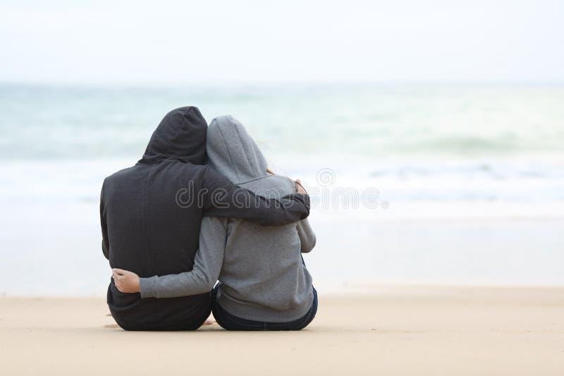 Par av tonåringar som kramar det hållande ögonen på havet royaltyfri fotografi