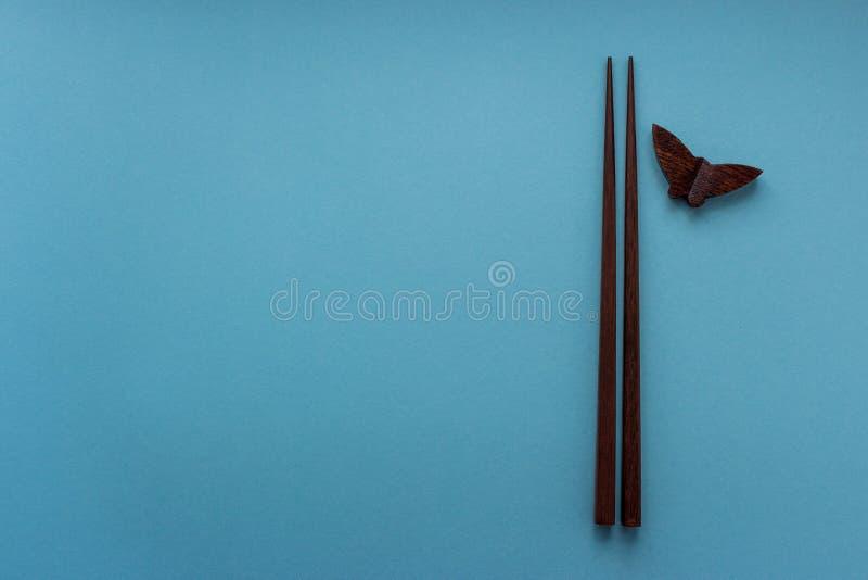 Par av träpinnar för japansk och kinesisk mat på blå bakgrund med kopieringsutrymme Begrepp för Asien matkultur royaltyfria foton