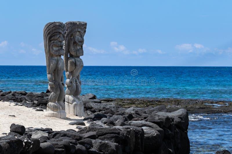 Par av trästatus Tikis, ställe av fristaden Honaunau, Hawaii Vit sand, vägg av svart lava vaggar, havet och blå himmel fotografering för bildbyråer