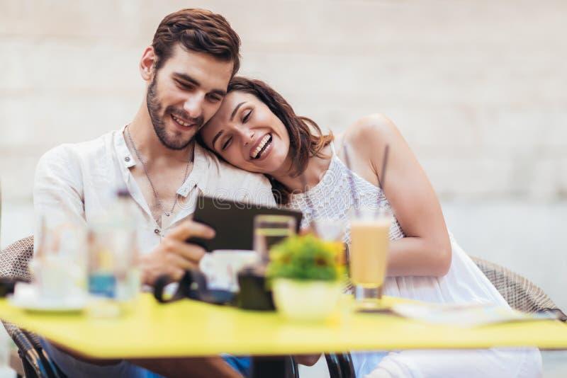 Par av turist- sammanträde i ett kafé som dricker kaffe och använder minnestavlan arkivbild