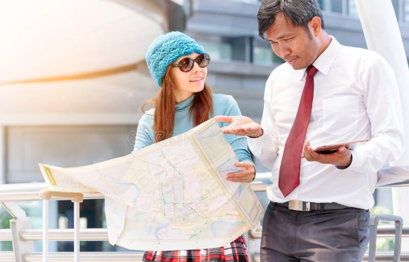 Par av turister som konsulterar en stad, vägleder sökande av lägen I royaltyfri foto