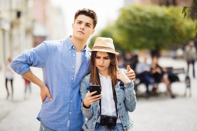 Par av turister som konsulterar smartphonegps i gatan som söker lägen i ny stad arkivfoto