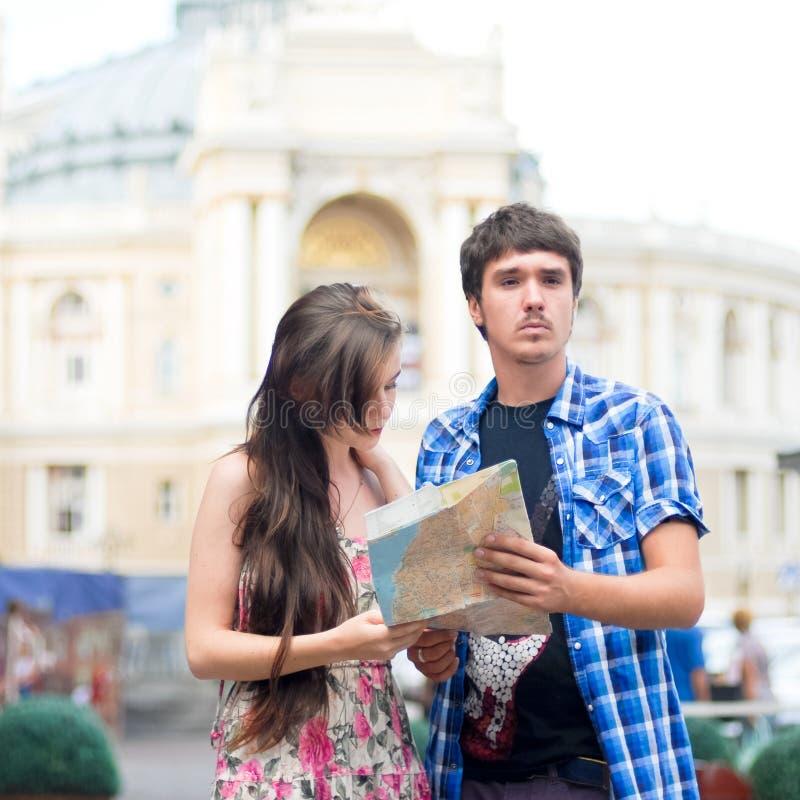 Par av turister som söker för riktningar på översikt royaltyfri foto