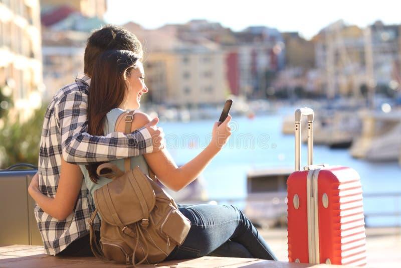 Par av turister som söker på en smart telefon royaltyfri bild