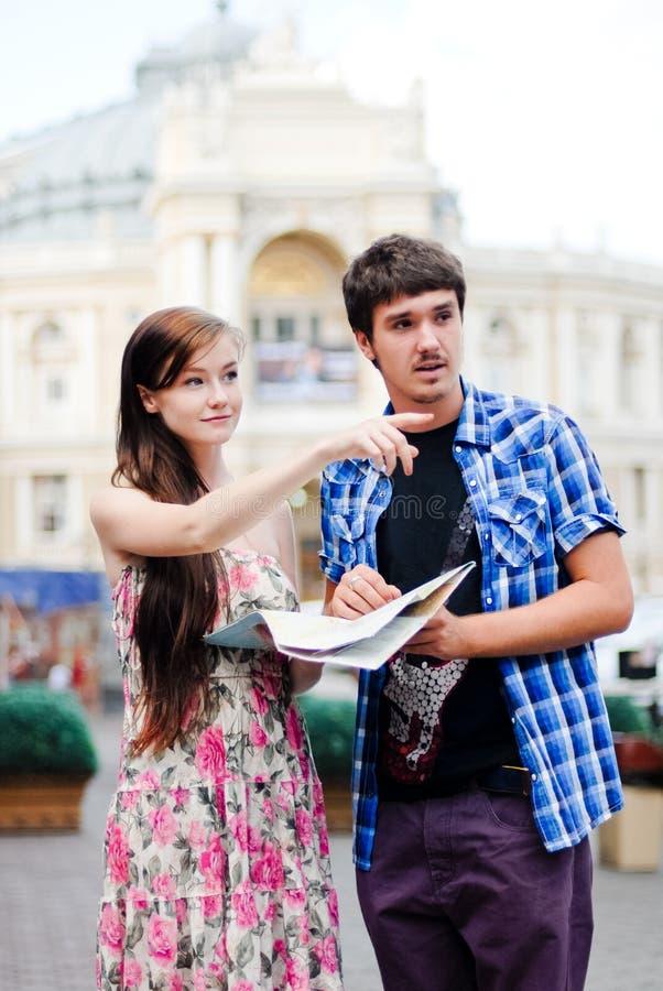 Par av turister som ser på översikt i stadsmitt royaltyfri foto