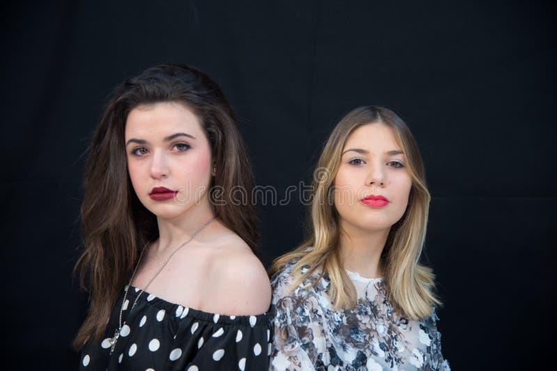 Par av två unga flickor, brunett och blondin, röda kanter och burgundy, ser in camera, svart bakgrund royaltyfri foto
