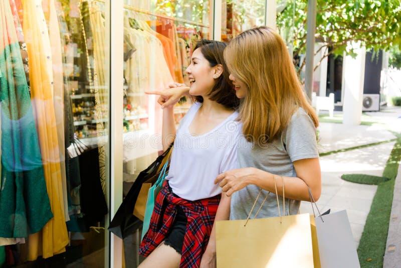 Par av unga asiatiska kvinnor gör shopping för en klänning i en utomhus- galleria i helgmorgonen arkivfoton