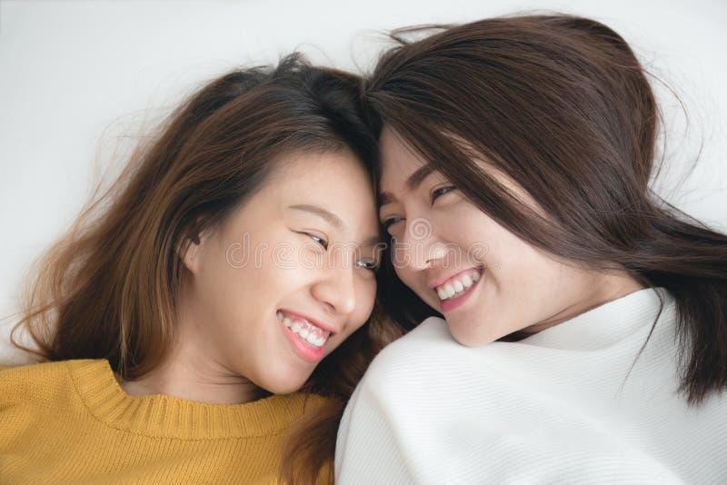 Par av unga asiatiska kvinnor på vit säng med lyckaögonblick, l arkivfoto