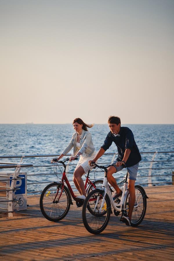 Par av unga hipsters som tillsammans cyklar på stranden på soluppgånghimmel på trädäcksommartid royaltyfri bild