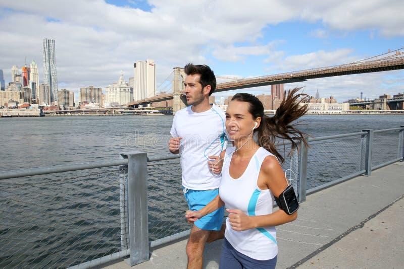 Par av unga joggers som kör på brooklyn, promenerar royaltyfria foton