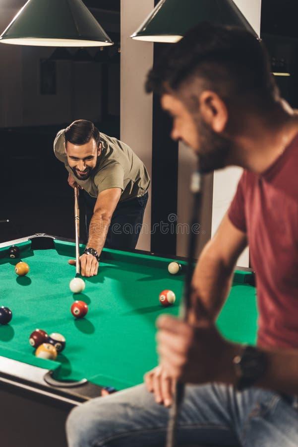 par av unga lyckade stiliga män som spelar i pöl royaltyfri bild
