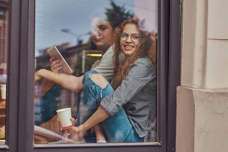 Par av unga studenter som dricker kaffe och använder en digital minnestavla, medan sitta på en fönsterfönsterbräda på en högskola arkivbilder