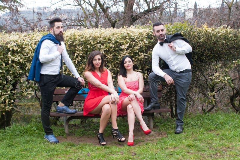 Par av unga vänner, kvinnor i rött klänningsammanträde på en bänk, män som står i elegant kläder royaltyfri foto