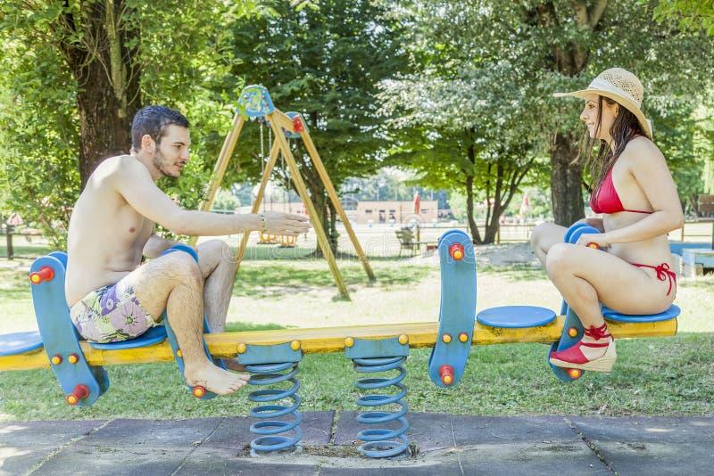 Par av unga vuxna människor har gyckel på en gungbräde arkivbilder