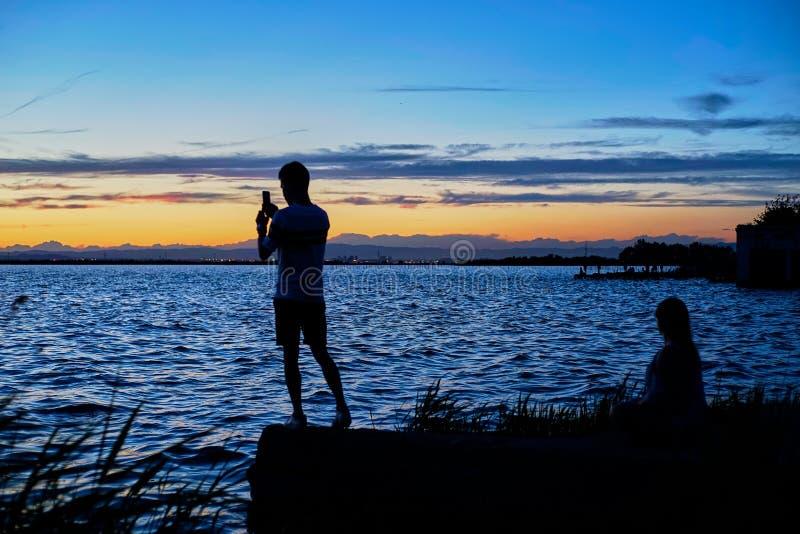 Par av ungdomarbeskådar solnedgången i Albuferaen av Valencia royaltyfria foton