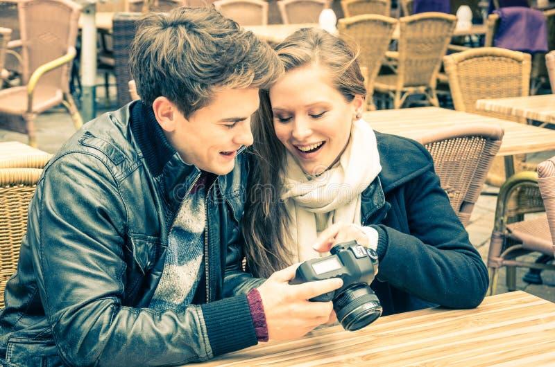 Par av vänner som håller ögonen på foto på en digital kamera royaltyfri bild