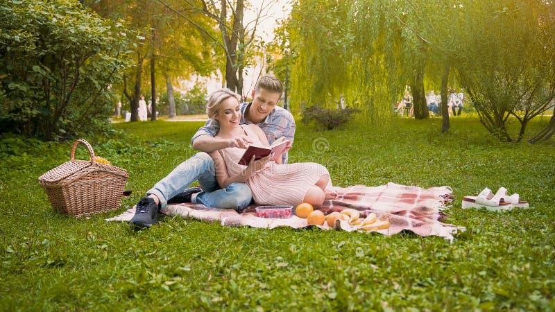 Par av vänner som läser nytt boksammanträde på filten under picknicken, romantiskt datum arkivfoto
