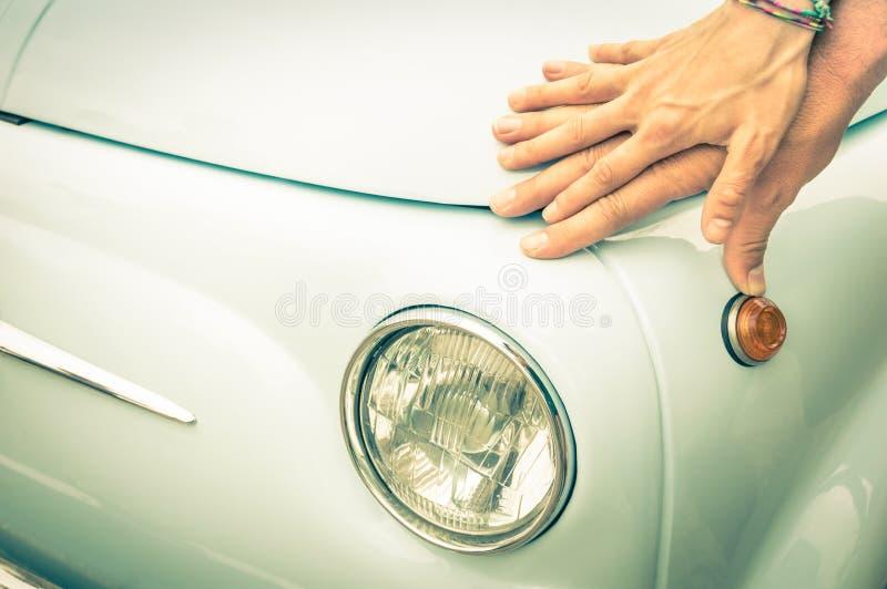 Par av vänner som rymmer händer på en retro klassisk bil för tappning royaltyfri fotografi