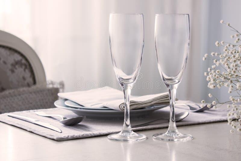 Par av vinexponeringsglas, champagneflöjter på brölloptabellen, modell royaltyfria foton