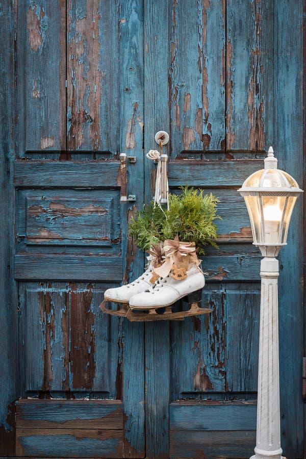 Par av vita isskridskor för tappning med julgarnering som hänger på den blåa lantliga dörren och en stor lykta fotografering för bildbyråer