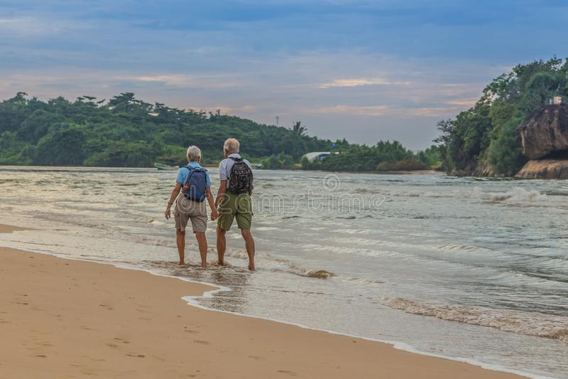 Par casado de personas mayores en la playa en la orilla del océano foto de archivo