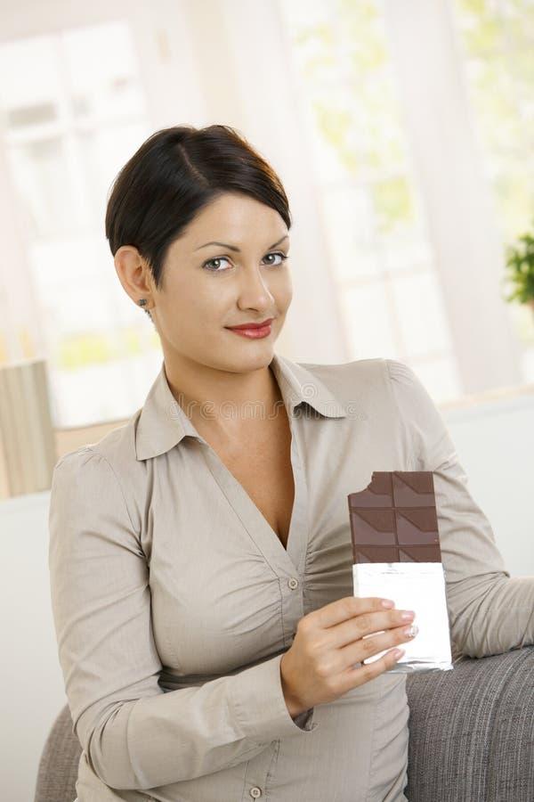 Par culpabilité regard du femme mangeant du chocolat images libres de droits