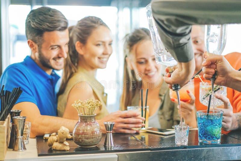 Par de los jóvenes de los amigos que beben los cócteles en el contador de la barra - camarero que prepara el cóctel colorido foto de archivo
