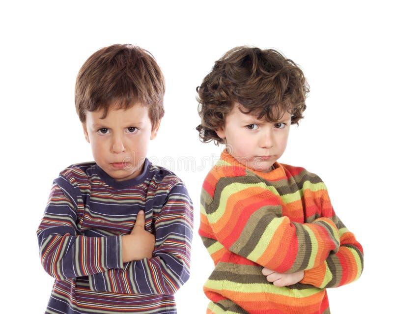 Par de niños enojados imagen de archivo