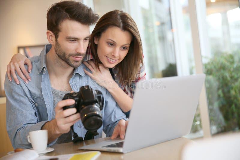 Par dopatrywanie brać fotografie na laptopie zdjęcie royalty free