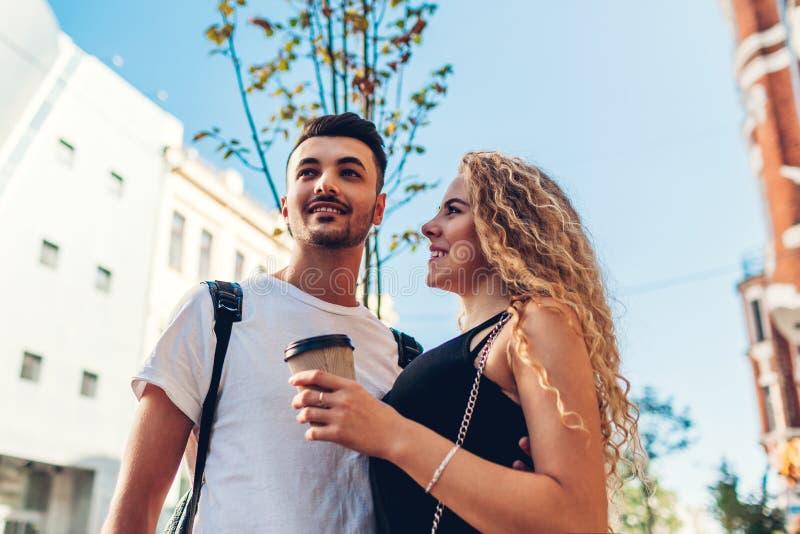 Par för blandat lopp av turister som går i stad Arabisk man och vit kvinna som dricker kaffe och utomhus kramar royaltyfri bild