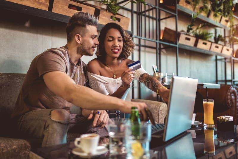 Par för blandat lopp som direktanslutet köper med kreditkorten och bärbara datorn i kafé royaltyfria bilder