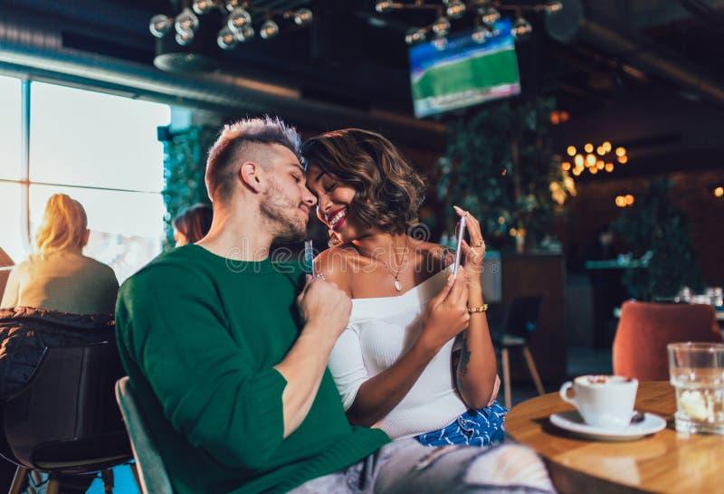 Par för blandat lopp som har gyckel på coffee shop Koppla ihop att tycka om på en coffee shop och att sitta på tabellen och att s arkivfoton
