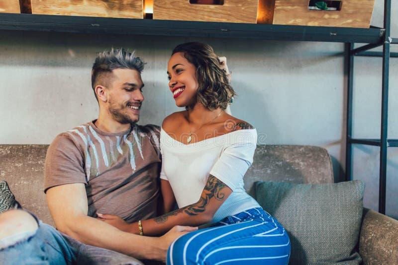 Par för blandat lopp som har gyckel på coffee shop Koppla ihop att tycka om på en coffee shop och att sitta på tabellen och att s arkivbilder