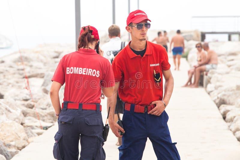Par för brandkämpar i Portugal Sesimbra strand arkivbilder