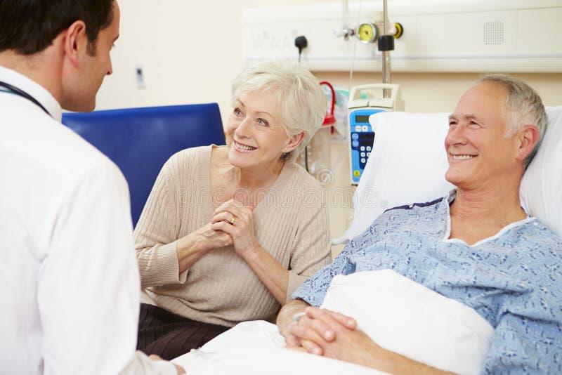 Par för doktor Talking To Senior vid sjukhussäng royaltyfri fotografi