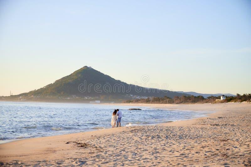 Par flörtar på stranden arkivbilder