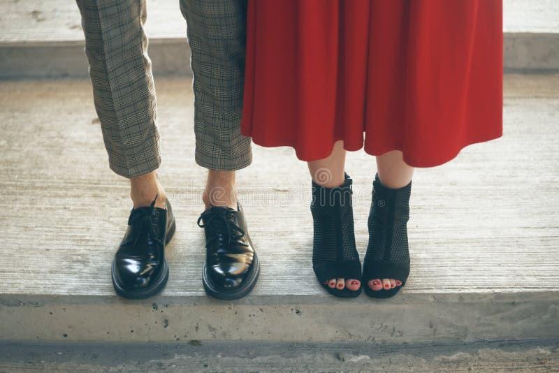 Par foots staget på gatan, stilfull moderiktig dräkt De mest härliga paren av skor Ben av ett ungt par i skor royaltyfria foton