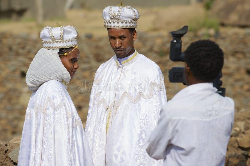 Par gör bröllopfotografi i traditionella klänningar, Axum, Etiopien arkivbild