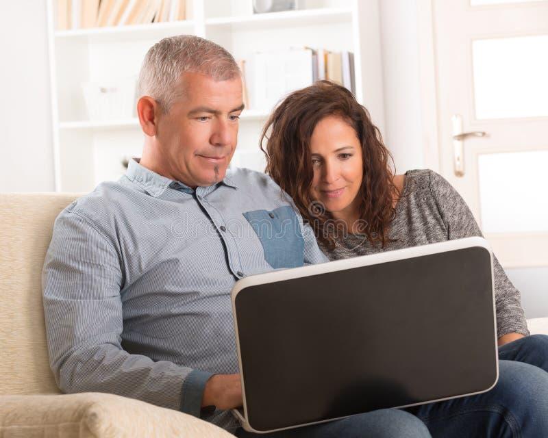 Par genom att använda bärbara datorn hemma royaltyfri foto