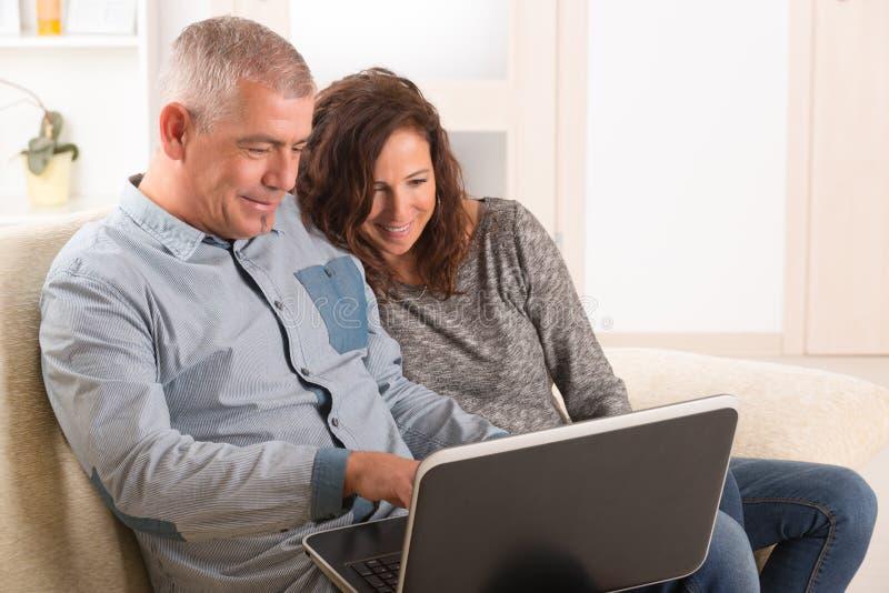 Par genom att använda bärbara datorn hemma royaltyfri bild