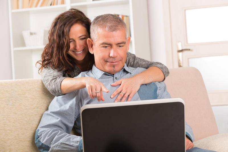 Par genom att använda bärbara datorn hemma royaltyfria foton