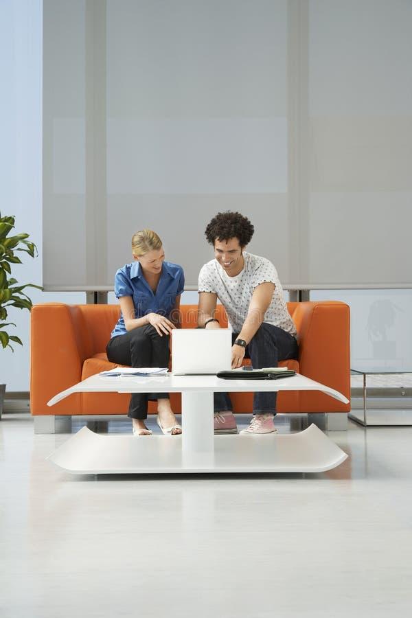 Par genom att använda bärbara datorn på orange Sofa At Office royaltyfri fotografi