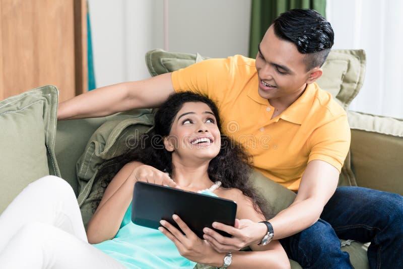 Par genom att använda den Digital minnestavlan hemma royaltyfria foton