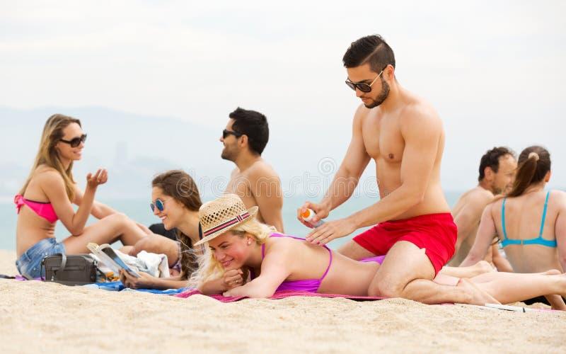 Par genom att använda kräm för solbränna royaltyfri bild
