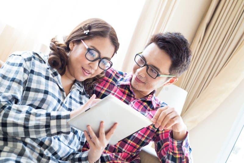 Par genom att använda minnestavlan i vardagsrum royaltyfria foton