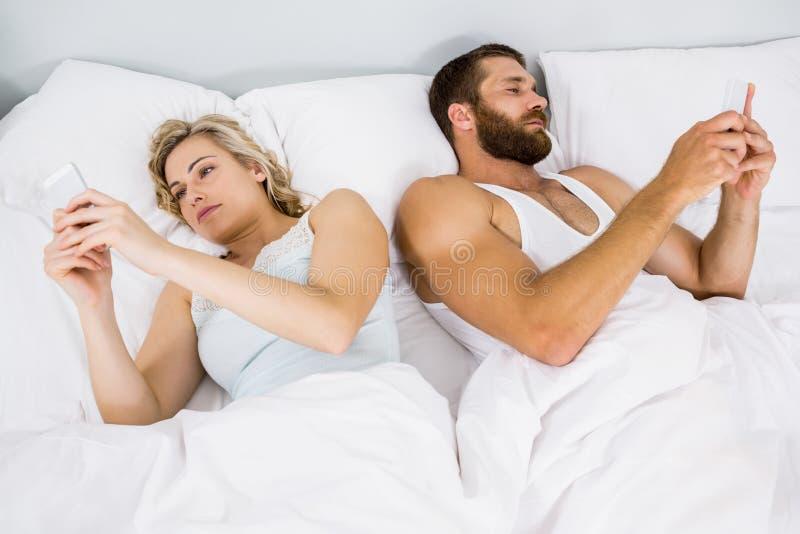 Par genom att använda mobiltelefonen på säng arkivfoto