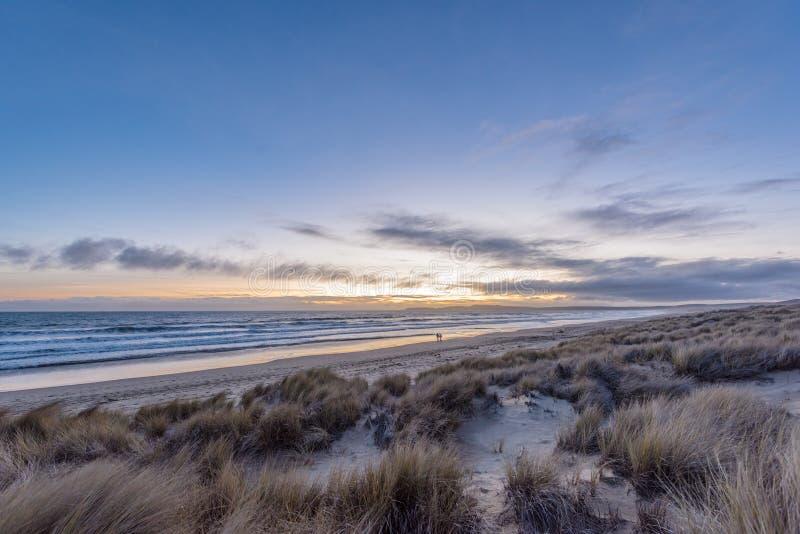 Par i avståndet som promenerar stranden på solnedgången royaltyfri fotografi