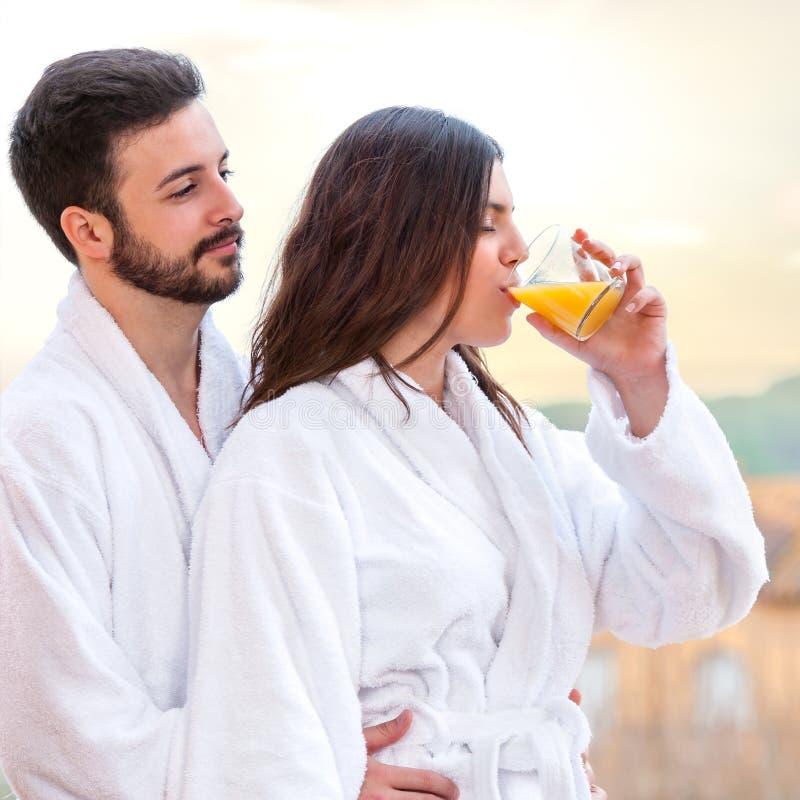 Par i badrocken som dricker fruktfruktsaft royaltyfri bild