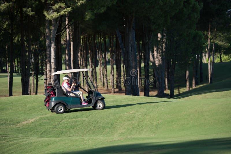 Par i barnvagn på golfbana royaltyfri fotografi